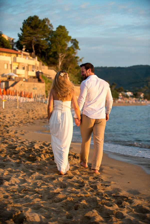 Couple walking on beach in Italy