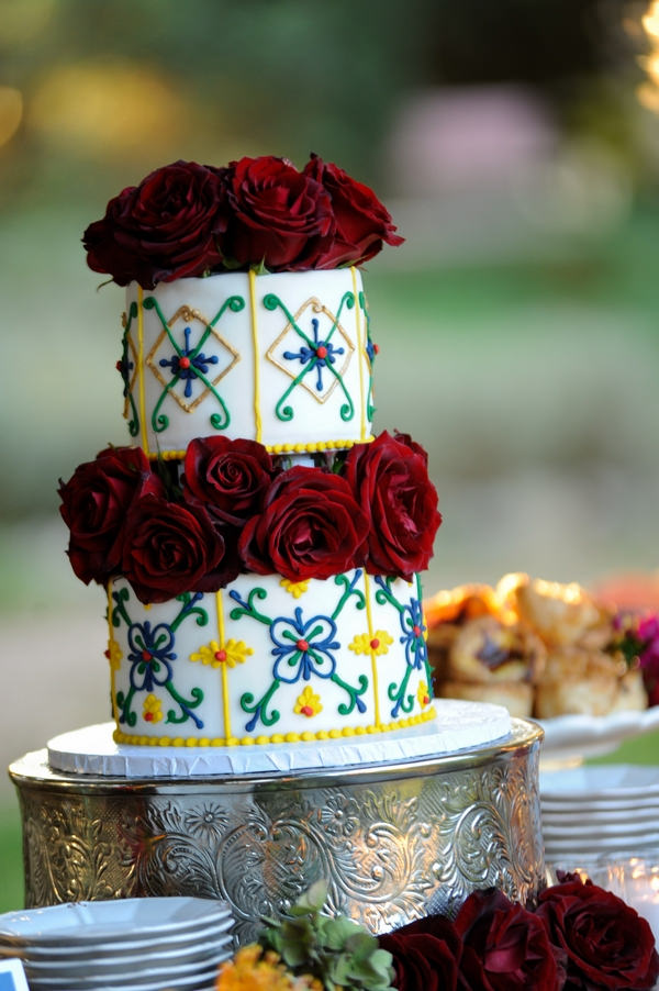 White Tiered Wedding Cake With Yellow And Blue Detail Red Flowers