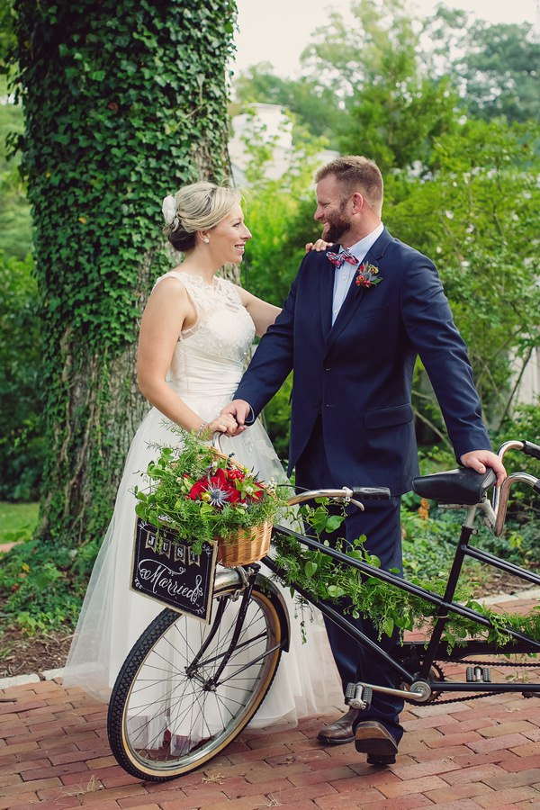 Bride and groom standing with vintage tandem bicycle