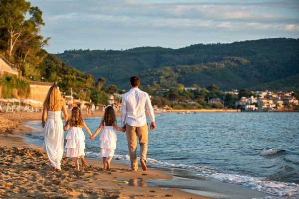 Family walking on beach in Italy