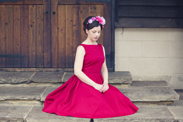 Bride in red vintage wedding dress sitting on floor