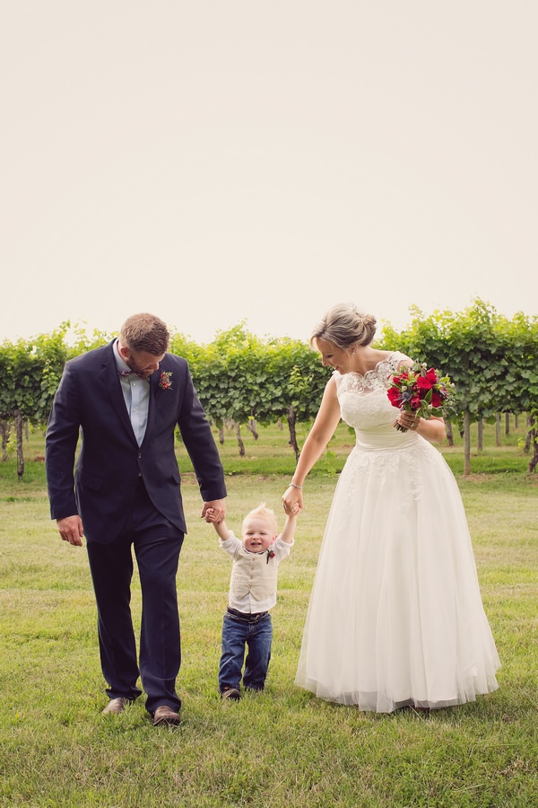 Young pageboy holding hands with bride and groom