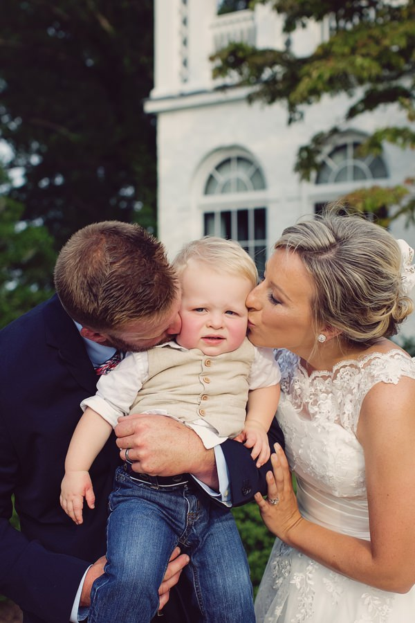 Bride and groom kissing pageboy on cheeks