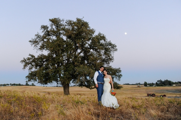 Bride and groom in field by tree