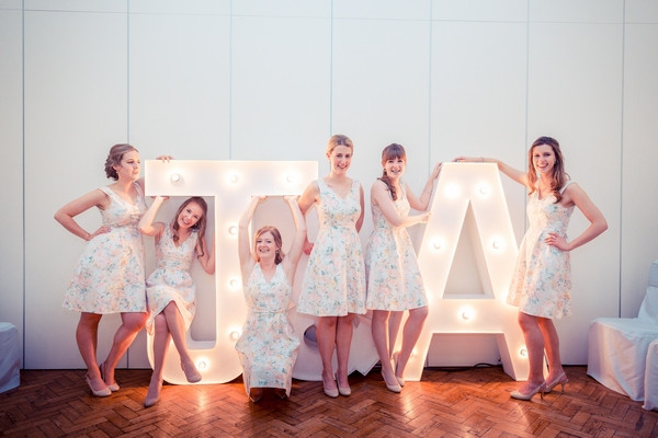 Bridesmaids posing with illuminated letters