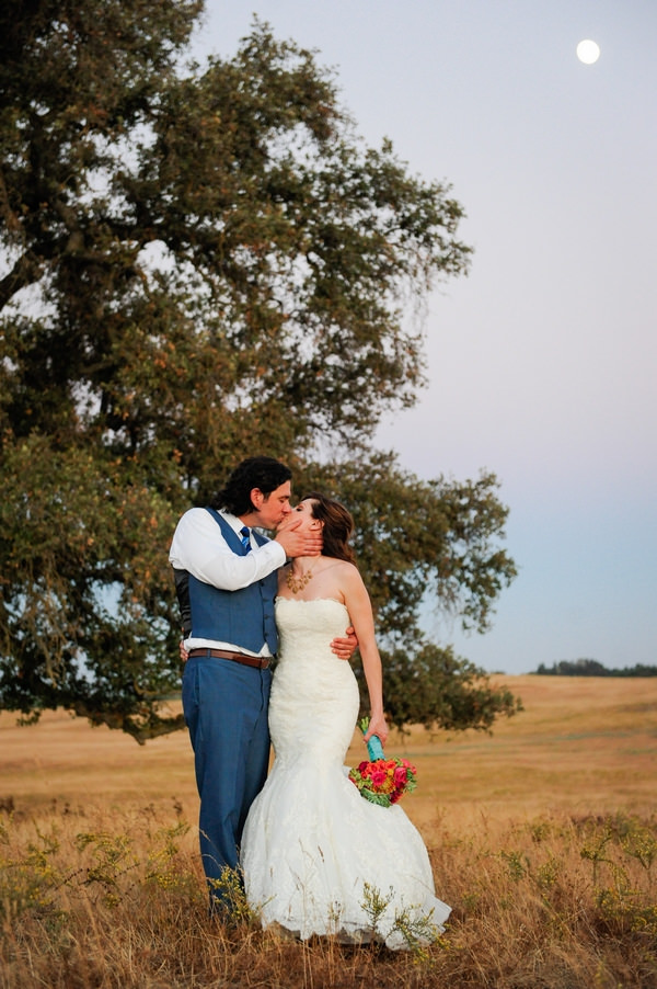 Bride and groom kiss by tree