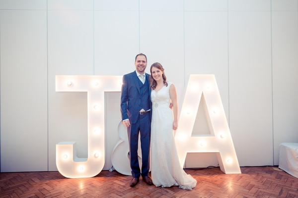 Bride and groom in front of large illuminated letters