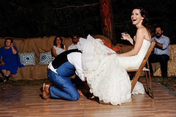 Groom under bride's dress to remove garter