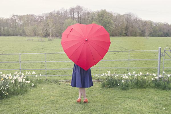 Bride behind red heart umbrella