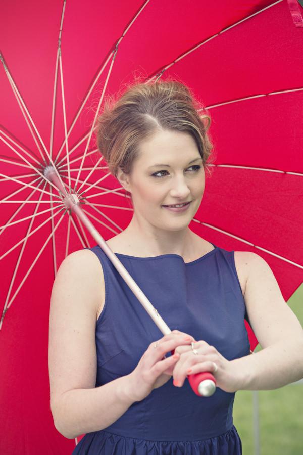 Bride holding red umbrella