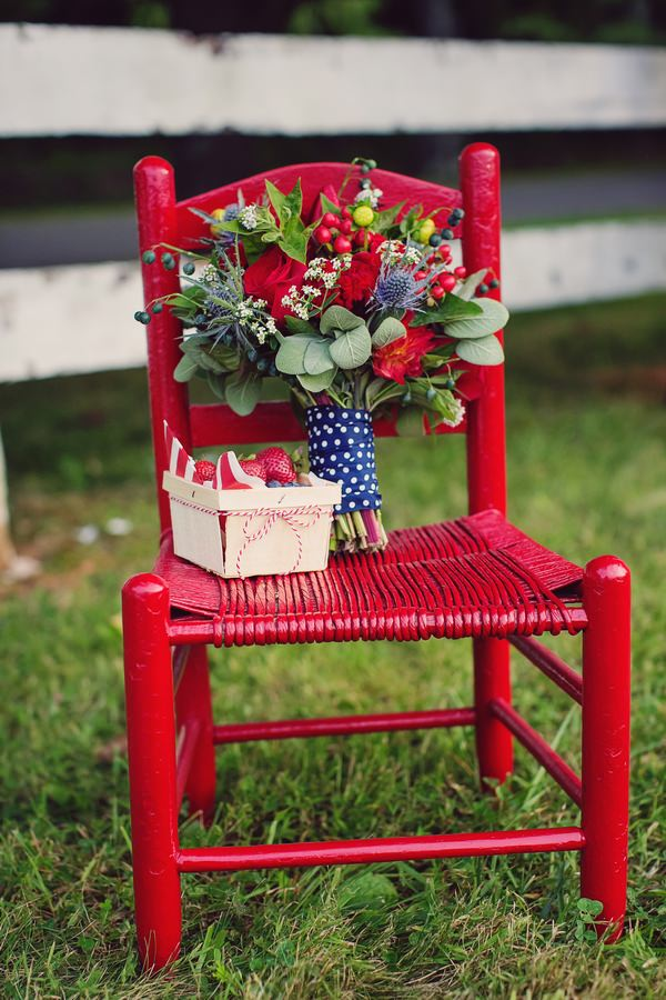 Bouquet and punnet of strawberries on red chair