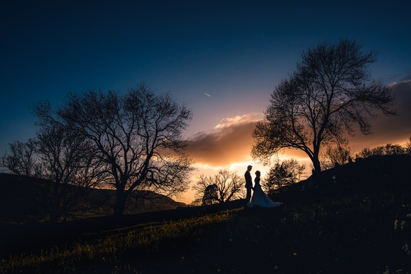 Bride and groom standing on hill at night - Picture by Andrew Keher Photography