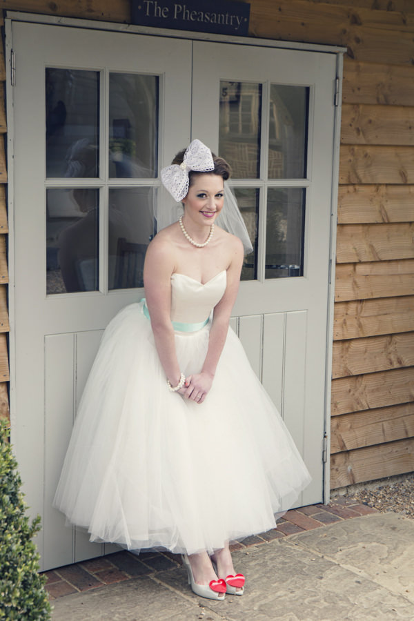 Bride wearing white wedding dress and large bow in hair