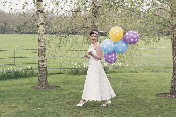 Bride holding spotty balloons