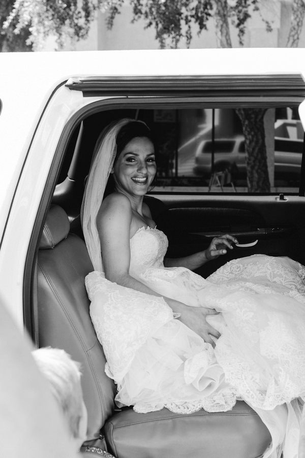 Bride in back of wedding car