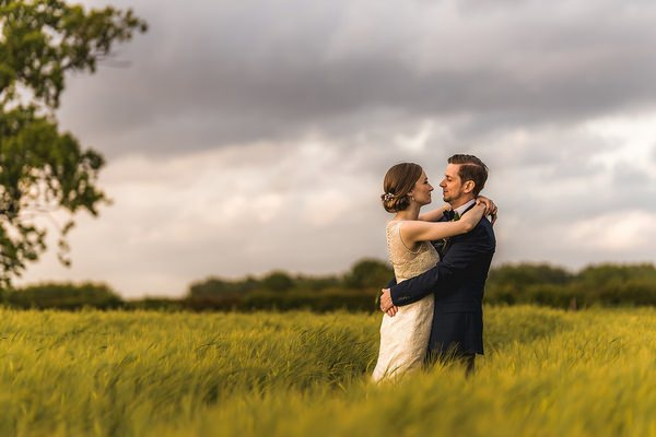 Bride and groom with arms around each other in field - Picture by Andrew Keher Photography
