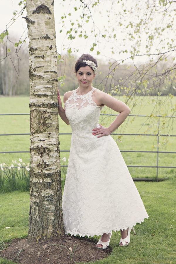 Bride standing next to tree