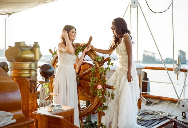 Two brides stdning by wheel on the Tall Ship Elissa