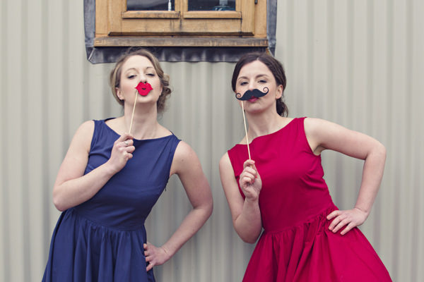 Brides wearing vintage red and blue wedding dresses holding lips and moustache to faces