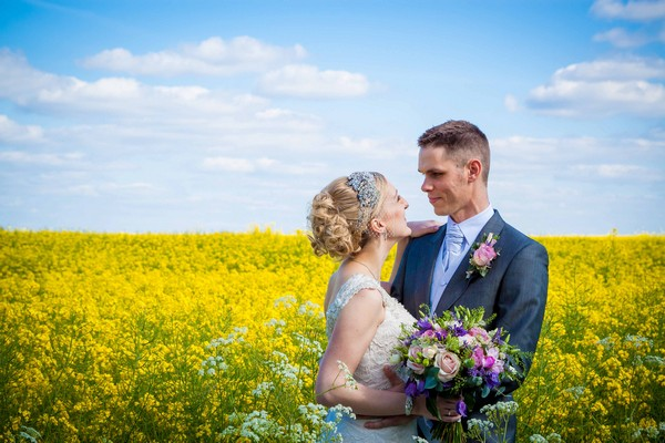 Bride and groom in yellow field - Picture by Amanda Karen Photography
