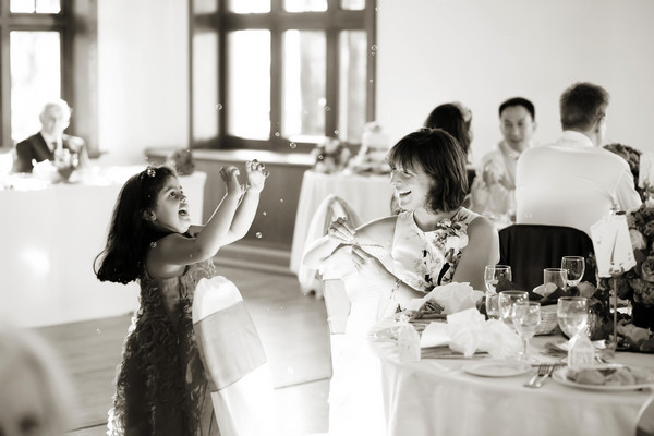 Young girl at wedding cathcing bubbles - Picture by Neil Walker Photography