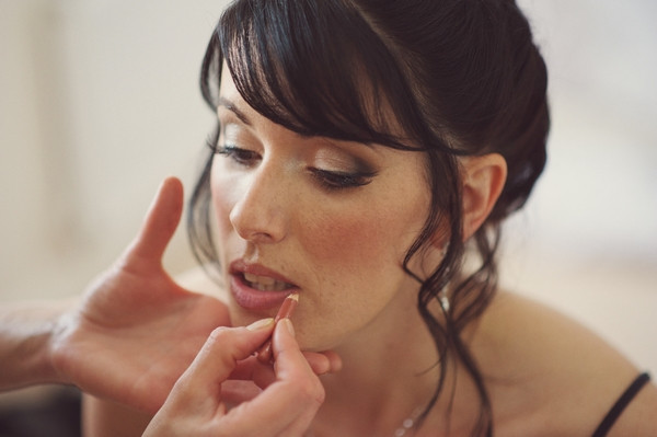 Bride having lip make-up done