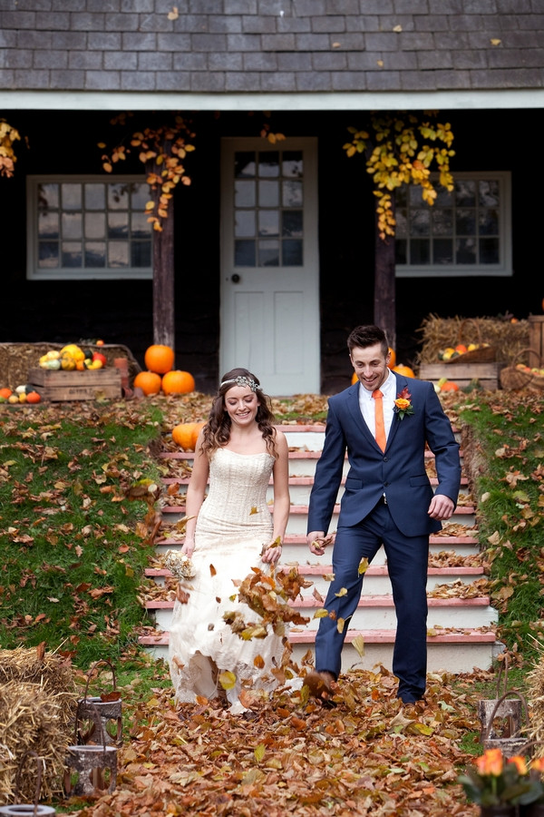 Bride and groom kicking autumn leaves