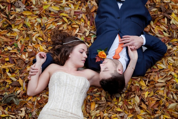 Bride and groom laying in autumn leaves