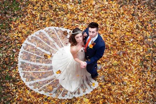 Bride and groom standing in autumn leaves