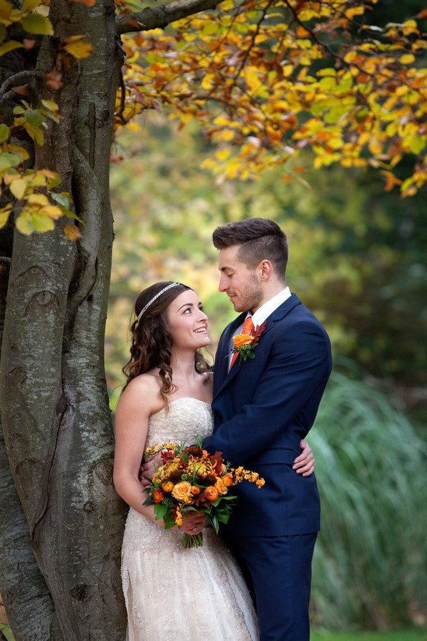Bride and groom standing under tree in autumn
