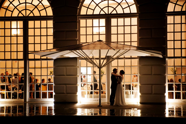 Bride and groom under parasol outside wedding venue at night - Picture by Neil Walker Photography