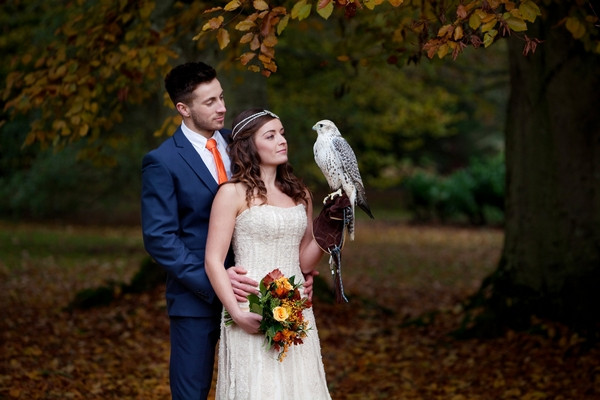 Bride and groom holding hawk