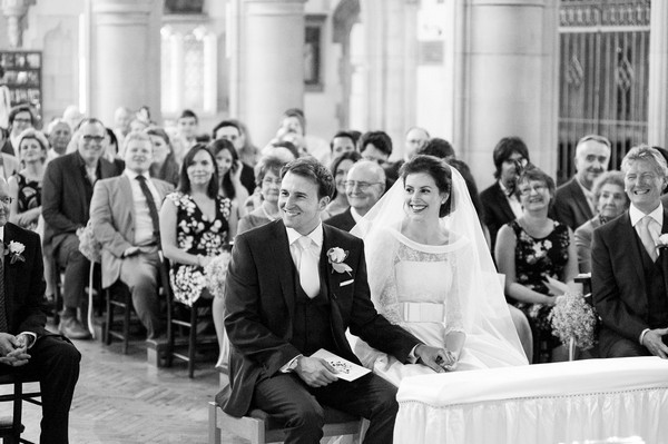 Bride and groom sitting at front of church