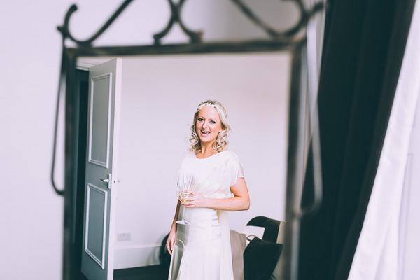 Smiling bride looking in mirror