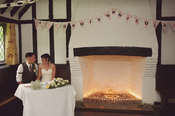 Bride and groom sitting by fireplace