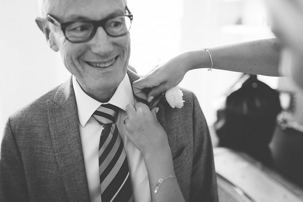 Bride's father having buttonhole put on