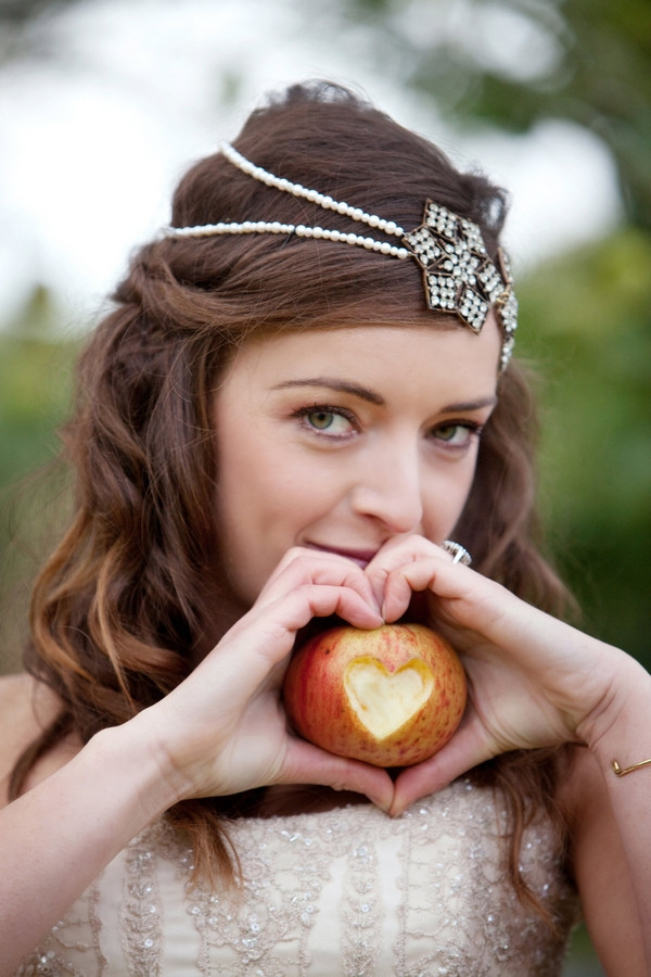 Bride holding apple with heart shape cut out