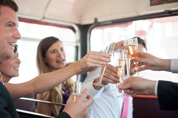 Toast with champagne on wedding bus