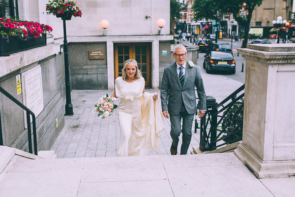 Bride and father walking up steps to Islington Town Hall
