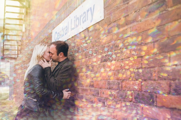Couple kissing against library wall