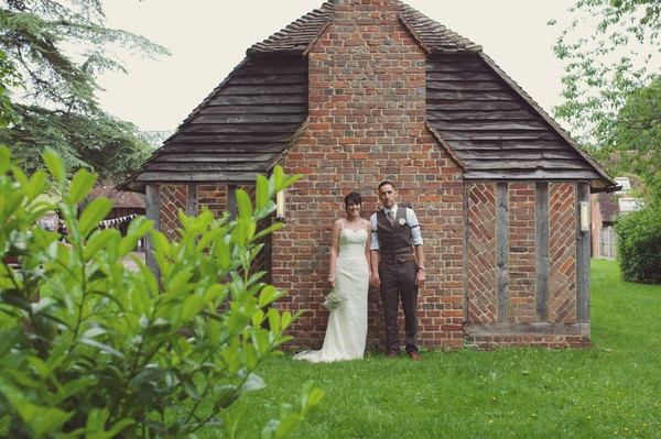 Bride and groom standing by wall of Chilham Village Hall in Kent