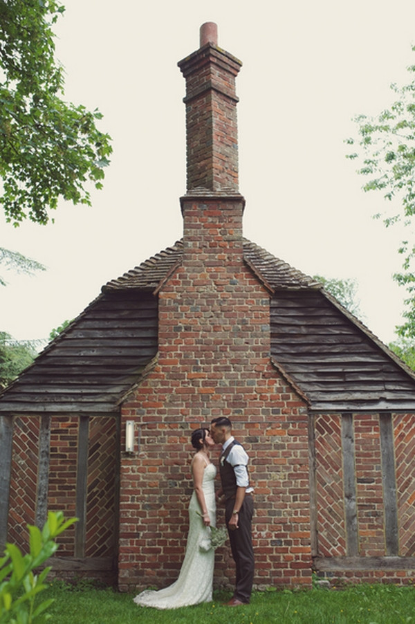 Bride and groom kissing by wall of Chilham Village Hall in Kent