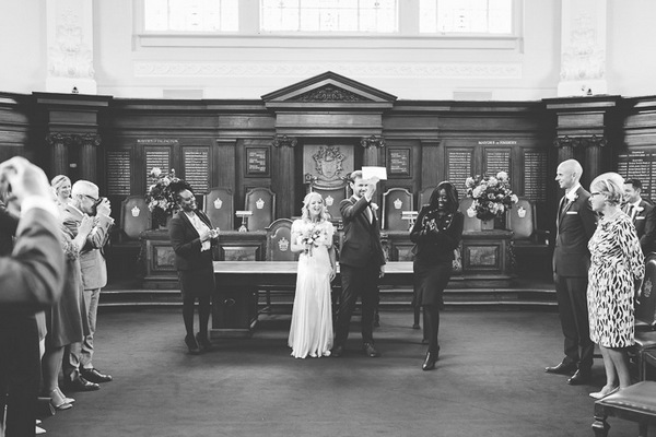 Groom holding up marriage certificate in Islington Town Hall