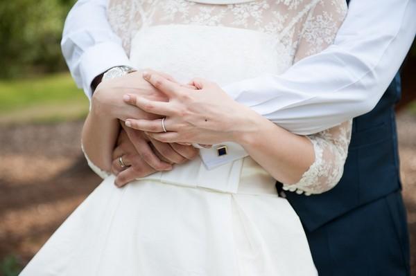 Bride holding grooms hands around waist