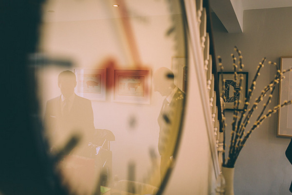 Reflection of groom in clock