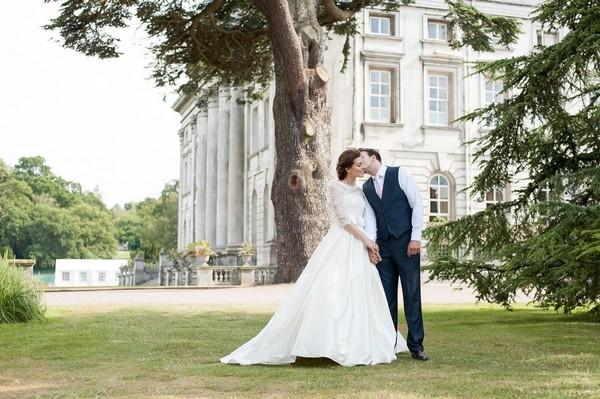 Groom kissing bride on cheek outside Moor Park Mansion
