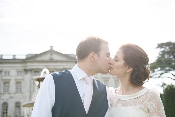 Bride and groom kiss outside Moor Park Mansion