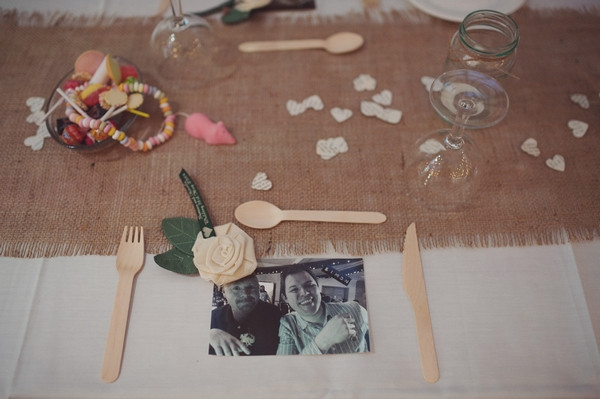 Photograph and wooden cutlery on wedding place setting
