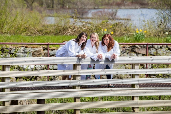 Bride and bridesmaids leaning on fence