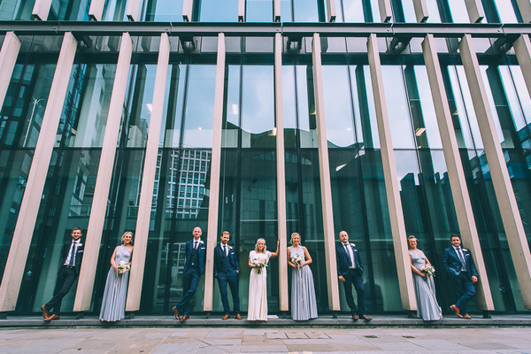 Bridal party in front of glass fronted building in London